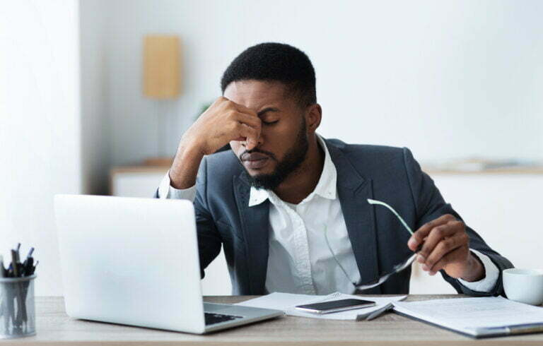 African american businessman tired of long time siting at work