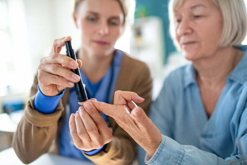 Caregiver and Patient Doing Self-Monitoring of Blood Glucose at Home