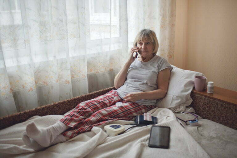Old woman in bed looking at screen of laptop and consulting with a doctor online at home, telehealth services during lockdown, distant video call, modern tech healthcare